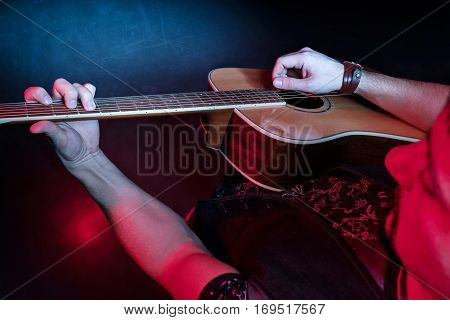 Guitarist playing an acoustic guitar, top view. The grunge style