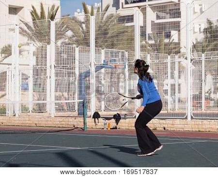 Nahariyya Israel - February 13 2016 : Woman playing tennis on the court and hits the racket on the ball