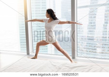 Young attractive woman practicing yoga after waking up, standing in Warrior Two exercise, Virabhadrasana II pose, working out, wearing white casual clothes, indoor full length, against floor window