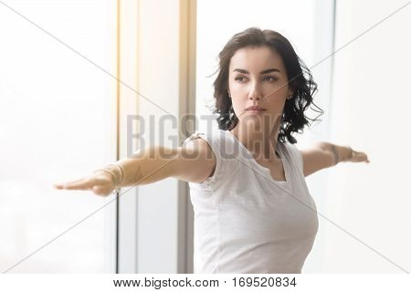 Young attractive woman practicing yoga after waking up in the morning, standing in Warrior Two exercise, Virabhadrasana II pose, working out, wearing white casual clothes, indoor, against sunny window