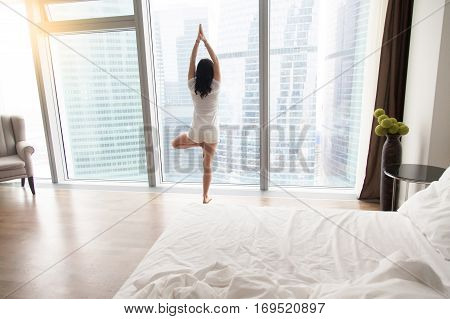 Young attractive woman practicing yoga at home after waking up, standing in Vrksasana exercise, Tree pose, working out, wearing white casual clothes, indoor full length, bedroom, unmade bed, rear view