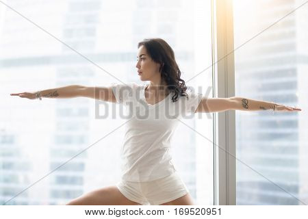 Young attractive woman practicing yoga in the morning, standing in Warrior Two exercise, Virabhadrasana II pose, working out, wearing white casual clothes, indoor, against window with city view
