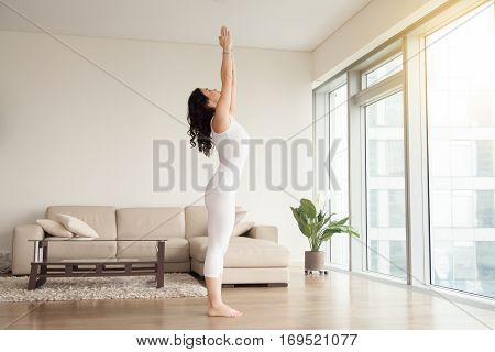 Young attractive woman practicing yoga at home, standing in mountain exercise, Tadasana pose, working out, wearing white clothes, indoor full length, in the center of living room