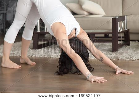 Young attractive woman practicing yoga at home, standing in Downward facing dog exercise, adho mukha svanasana pose, working out, wearing white clothes, indoor in the living room. Close up