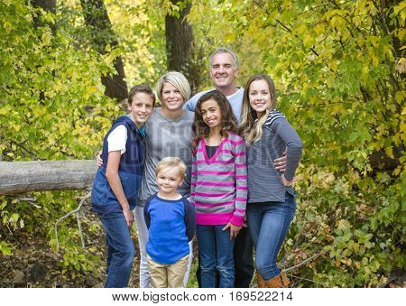 A smiling, happy, large beautiful family portrait. Standing together and hugging each other outdoors with a forest in the background