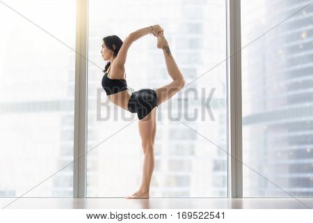 Young attractive woman practicing yoga, standing in Natarajasana exercise, Lord of the Dance pose, working out, wearing sportswear, black tank top, shorts, full length, floor window with city view