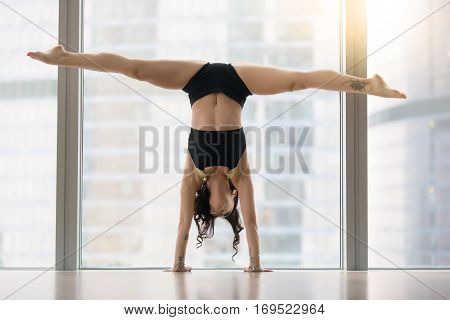 Young modern dancer attractive woman practicing, doing handstand exercise, dance pose, working out, wearing sportswear, black tank top, shorts, indoor full length, near floor window with city view