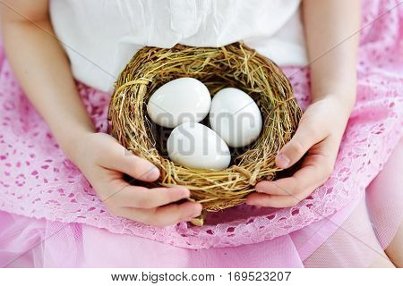 Cute Little Girl Holding A Nest With White Easter Eggs At Home On Easter Day
