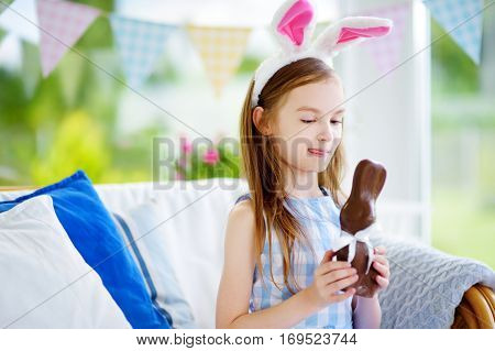 Cute Little Girl Wearing Bunny Ears Eating Chocolate Easter Rabbit