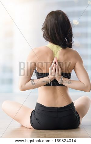 Young attractive woman practicing yoga, sitting in Ardha Padmasana exercise, Half Lotus pose with namaste behind back, working out, wearing sportswear, black tank top, shorts, near window, rear view