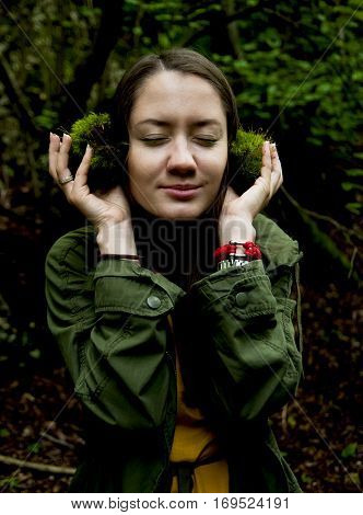 young girl listening to the music of nature with headphones from moss