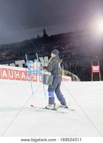STOCKHOLM SWEDEN - JAN 31 2017: SOfficials spreading salt to prepare the ski used for parallel slalom at the Alpine Audi FIS Ski World Cup. January 31 2017 Stockholm Sweden