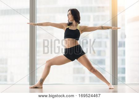 Young attractive woman practicing yoga, standing in Warrior Two exercise, Virabhadrasana II pose, working out, wearing sportswear, black tank top, shorts, full length, near floor window with city view