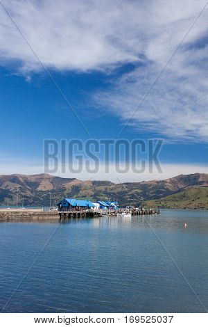 The Akaroa pier in a warm sunny day. Just 75 kilometres from the city of Christchurch, New Zealand, Akaroa is a historic French and British settlement nestled in the heart of an ancient volcano.