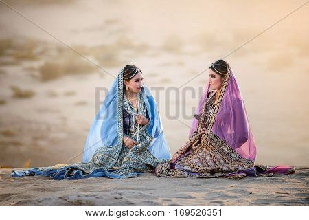 portrait of beautiful Arabian girls in traditional suit with valuable accessory Persian girls in desert