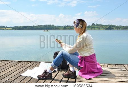 Traveler with a compass on the wooden jetty
