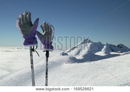 Ski gloves on ski poles on the background of southern slope Aibga Ridge of the Western Caucasus at Rosa Khutor Alpine Resort