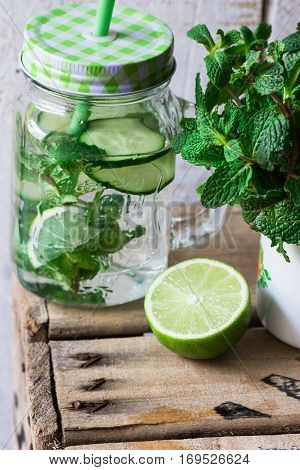 Mason jar mug with infused detox cucumber water with lime and mint ingredients wood box spring outdoors cleansing