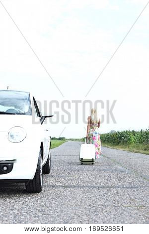 Rear view of woman with luggage leaving broken down car on country road