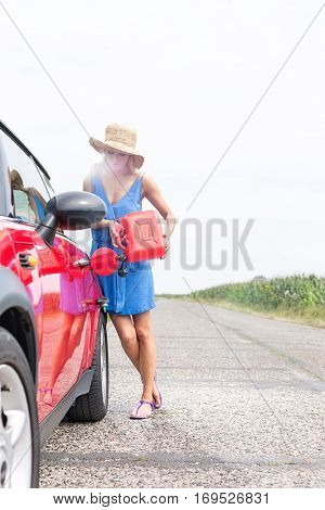 Full-length of woman refueling car on country road against clear sky