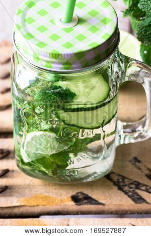 Jar mug with refreshing detox cucumber water with fresh mint and lime wood background outdoors spring cleansing