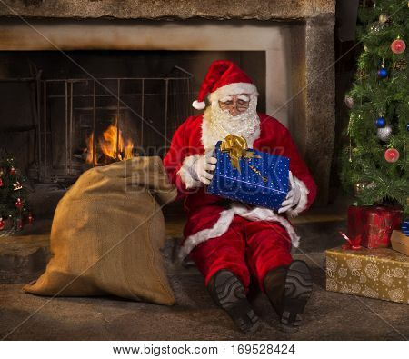 Santa claus is opening a gift for christmas behind fireplace.