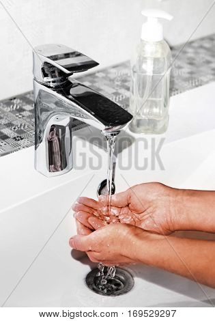 woman washing hands in sink, close up view