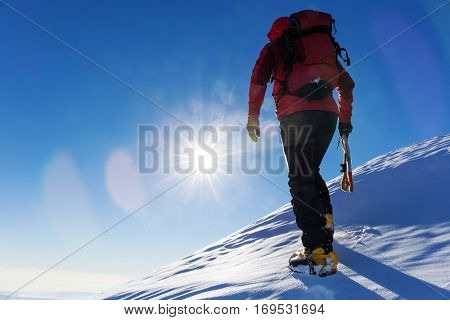 Extreme winter sports: climber at the top of a snowy peak in the Alps. Concepts: determination, success, brave.