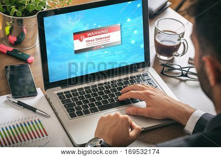 Man working with a laptop. Virus alert on the screen