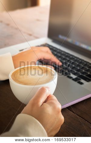 Woman working with laptop and hot coffee stock photo