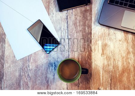 Coffee break time to take pause from your work - cup with hot coffee drink on office desk among smartphone and laptop computer
