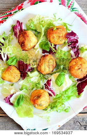 Fried potato balls, salad mix, basil on a plate. Delicious fried mashed potato balls with pumpkin seeds. Vertical photo. Top view