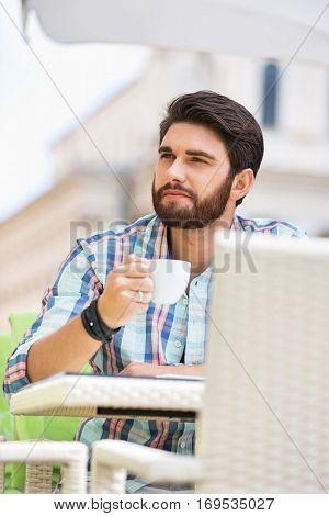 Man looking away while having coffee at sidewalk cafe