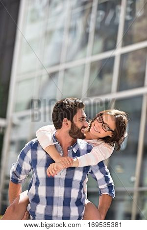 Happy couple looking at each other while enjoying piggyback ride in city