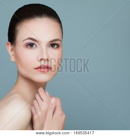 Beautiful Model Woman with Healthy Skin on Blue Background. Spa Beauty and Facial Treatment Concept