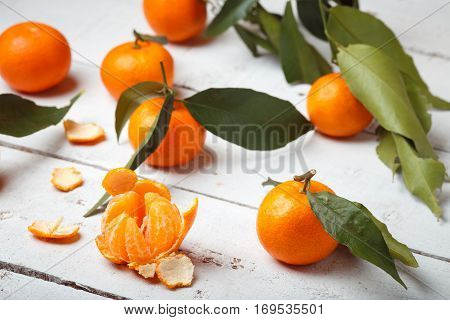 mandarins with leaves on white woodwn background.