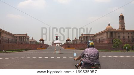 NEW DELHI, INDIA. 30 may 2009:  Delhi Government buildings. Biker with the child in the foreground.  Gate, Rashtrapati Bhavan, Rajpath, New Delhi, India