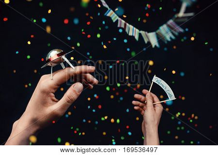 Woman hands holding a tiny UFO and a welcoming sign on a dark background with scattered confetti.