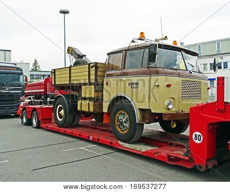 Chemnitz, Germany - October 4, 2015: A historic Skoda truck of the type 706 RT is loaded on a modern low loader. The loader is parked in a parking lot in Chemnitz (Germany).