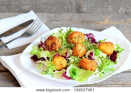 Crispy fried potato balls recipe. Home fried mashed potato balls with pumpkin seeds served with fresh lettuce and basil on a plate. Cutlery, napkin on vintage wooden table
