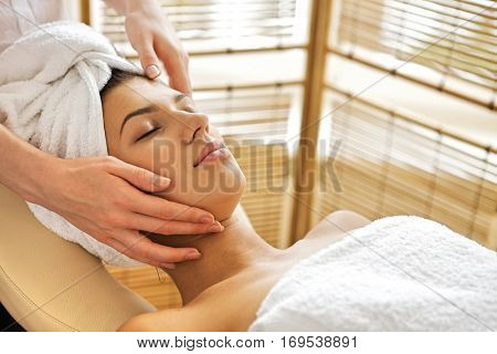 Young woman receiving massage, eyes closed