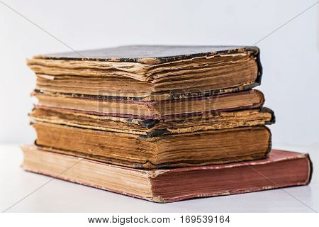 close-up of a stack of several very old and worn books