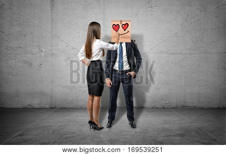 Businesswoman is drawing an enamored face on the box which hides a businessman's face. Leadership. Business management. Teamwork