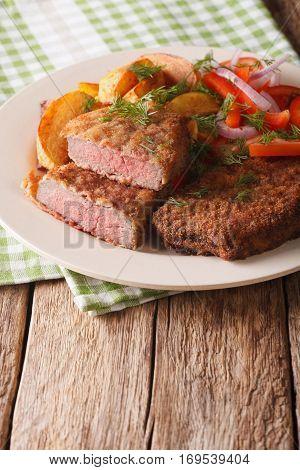 Rump Steak In Breadcrumbs And Fresh Vegetables, Baked Potatoes Close Up. Vertical
