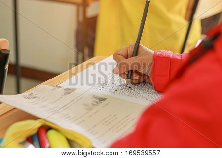 student testing in exercise exams answer sheets on table exam in classroom Thai education