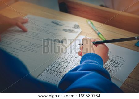 Thai students writing on a paper for exams and admissions in high school Thailand