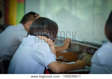 Thai students writing on a paper for exams and admissions in high school Thailand : education concept
