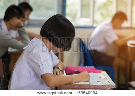 Thai students writing on a paper for exams and admissions in high school with uniform Thailand : education concept