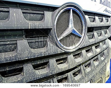 Chemnitz, Germany - October 4, 2015: Muddy front end of a truck of the type Mercedes-Benz Arocs with the typical Mercedes star. Mercedes-Benz is a trademark of vehicles of Daimler AG.