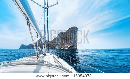 Sailing vessel moves in a sea under power towards the island